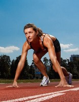 Female runner crouches in readiness on the start line of a race