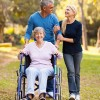 MIddle-aged couple walking arm in arm through a park while pushing their mother in a wheelchair