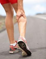 A runner massaging his calf after a sudden injury mid-run