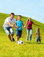 Healthy and happy family running through field chasing a soccer ball