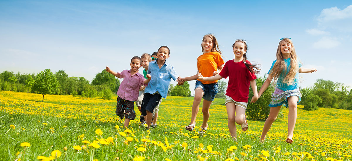 happy and healthy kids running across a field holding hands